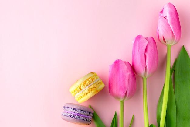Strauß rosa tulpen mit makronen. tulpen in einem waffelglas eis. frühlingszusammensetzung. frühlingskonzept. tulpen in einer vase mit süßigkeiten.