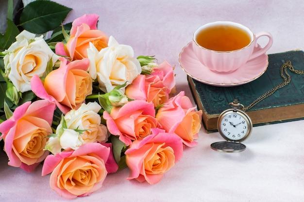 Strauß rosa und cremefarbener rosen, eine tasse tee, ein buch und eine taschenuhr