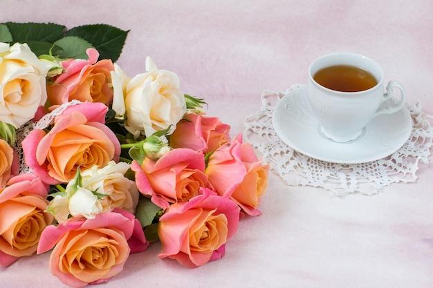 Strauß rosa und cremefarbener rosen und eine tasse tee