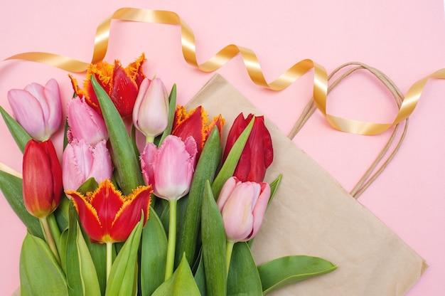 Strauß rosa und roter tulpen und eine papiertüte auf einem rosa