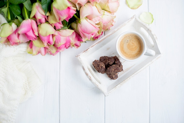 Strauß rosen auf weißem hintergrund und eine tasse kaffee mit schokolade