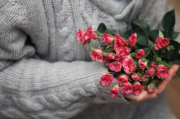 Strauß rosenbusch in weiblichen händen auf einem hintergrund von strickpullovern