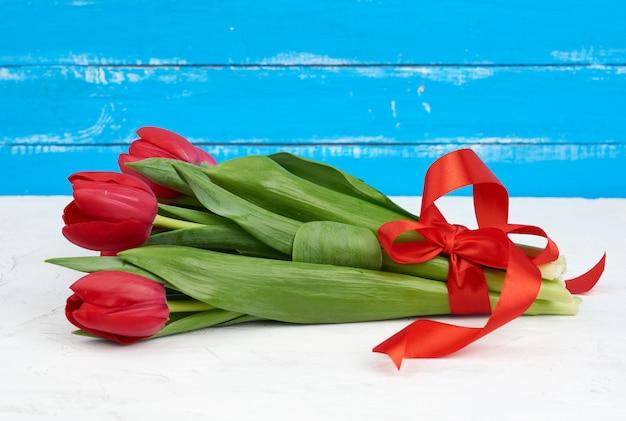 Strauß rot blühender tulpen mit grünen stielen und blättern, gebunden mit einem roten seidenband