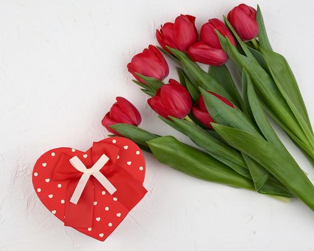 Strauß roter blühender tulpen mit grünen blättern, verpacktes geschenk in braunem bastelpapier auf weißem hintergrund