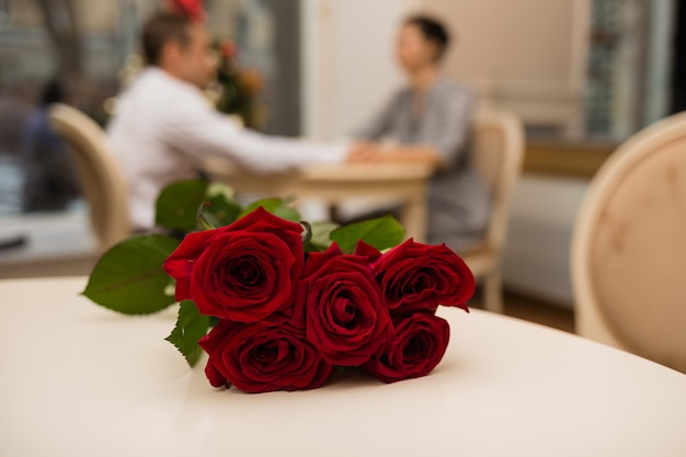 Strauß roter rosen auf dem hintergrund eines jungen paares am tisch