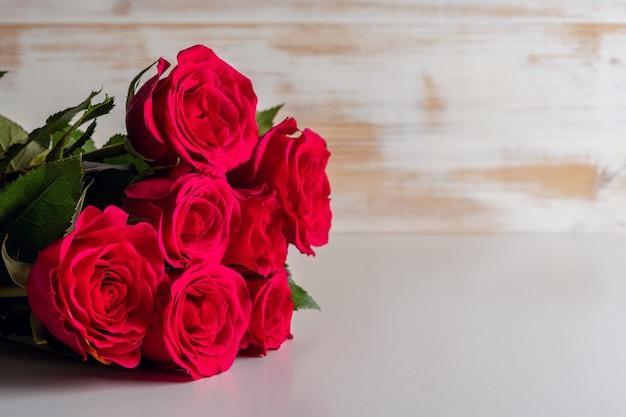 Strauß roter rosen auf holztisch.