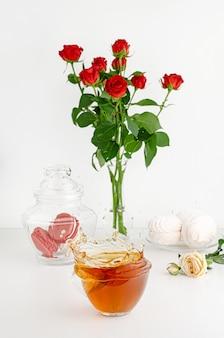 Strauß roter rosen, teespritzer in einer tasse und süße desserts