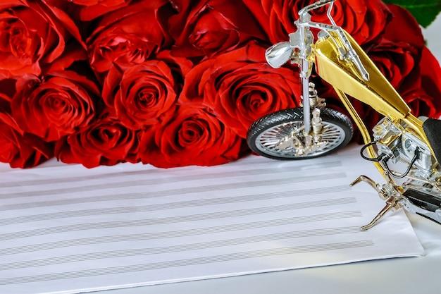 Strauß roter rosen und ein motorrad auf einem blatt für musiknoten. glückwunsch an den musiker. platz kopieren.