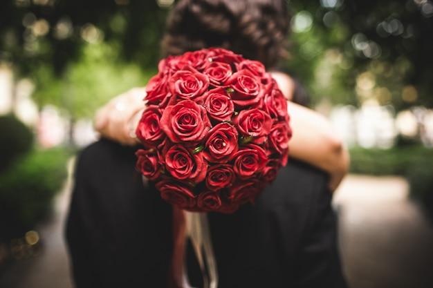 Strauß roter rosen von einer frau beim umarmen ihres geliebten gehalten.