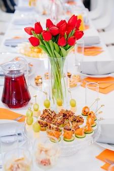 Strauß roter tulpen auf festlichem tisch. servieren des tisches mit vorspeisen, häppchen, salaten in gläsern.