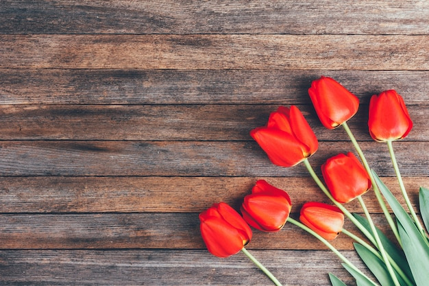 Strauß roter tulpen auf hölzernem retro-schmutz mit kopienraum.