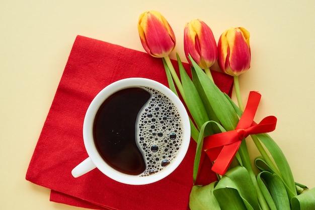 Strauß roter tulpen mit schwarzem kaffee auf licht