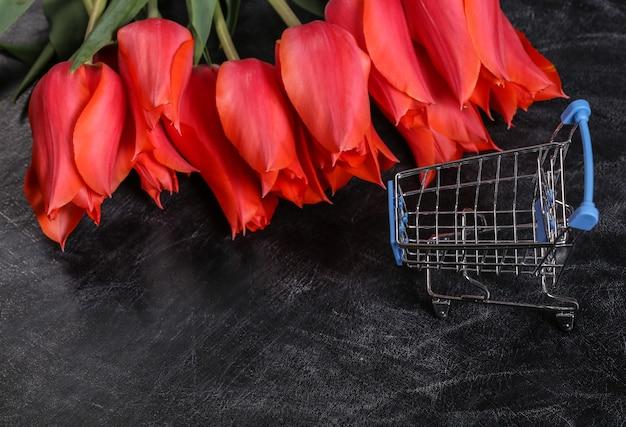 Strauß roter tulpen und einkaufswagen auf kreidetafelhintergrund