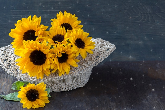 Strauß sonnenblumen in einem strohhut