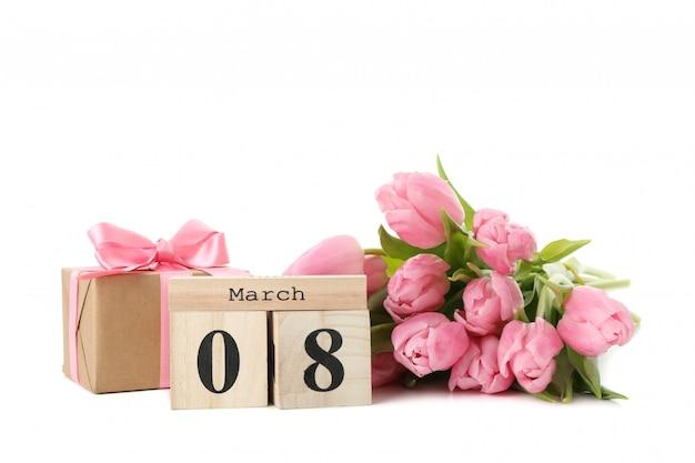 Strauß tulpen, holzkalender und geschenkbox lokalisiert auf weißem hintergrund