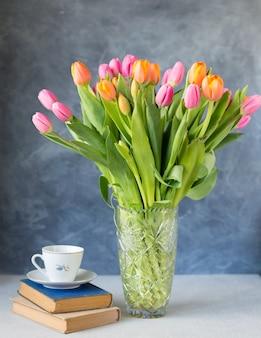 Strauß tulpen in vase und bücher auf dem tisch. frühlingsblumen . blumenstrauß in vase. rosa und orange blühende flora. gemütliches stillleben. speicherplatz kopieren. urlaubsgruß.