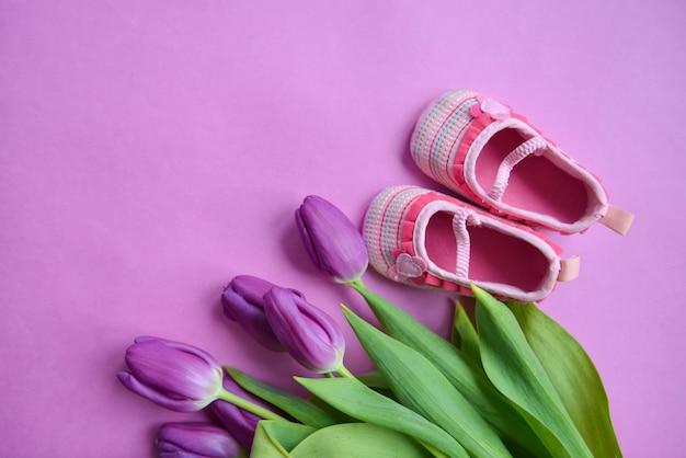Strauß tulpen und kinderschuhe für mädchen