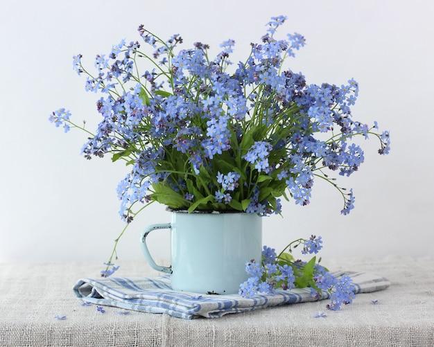 Strauß vergissmeinnicht in einem blauen becher. zarte sommerkomposition.