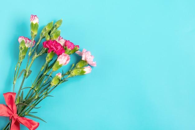 Strauß verschiedener rosa nelkenblumen auf blauem hintergrund draufsicht flache lage