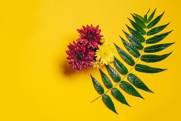 Strauß von rosa und gelben gerberablumen und einem zweig mit grünen blättern auf gelbem grund