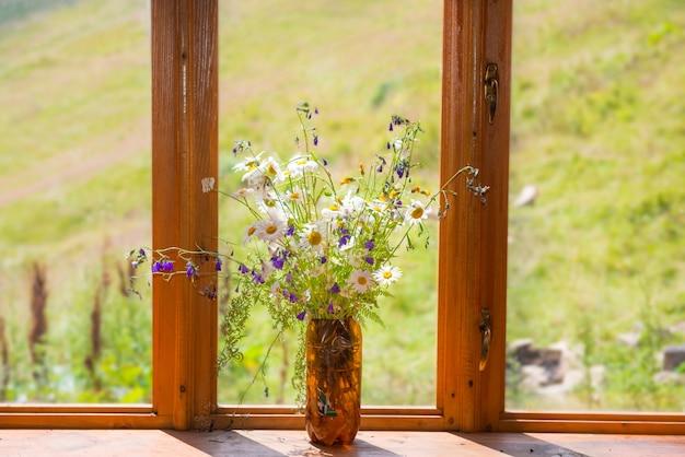 Strauß weißer blumen gänseblümchen auf holzfensterbank zu hause