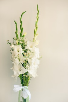 Strauß weißer gladiolen. zarte gladiolenblüten des weiß auf weißem hintergrund