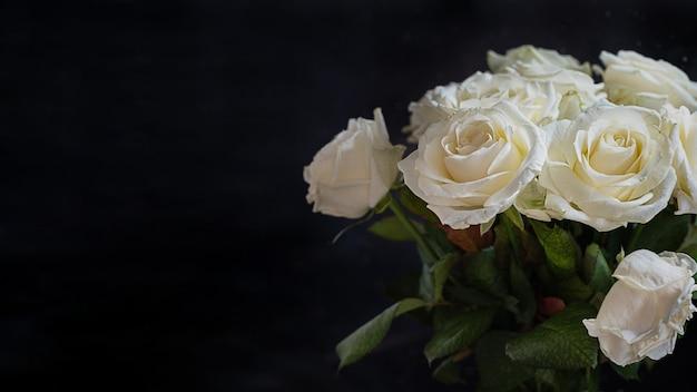 Strauß weißer rosen auf dunkler oberfläche
