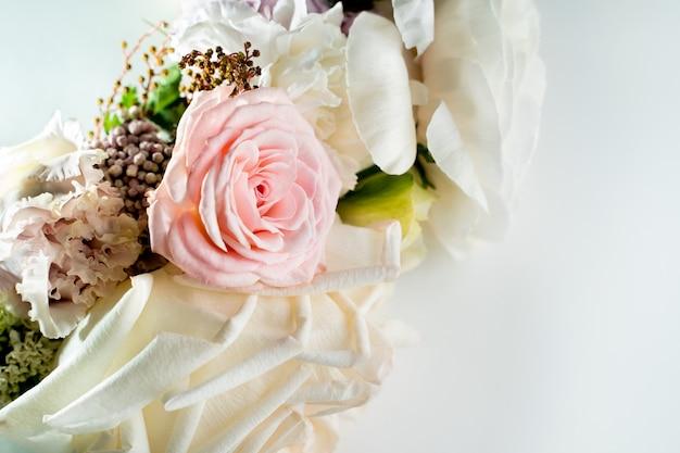Strauß weißer rosen, die auf dem weißen tischnahaufnahmekopierraum liegen lying