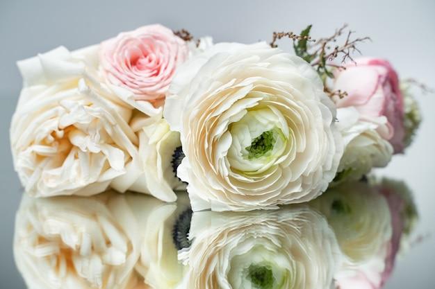 Strauß weißer rosen, die auf der spiegelnahaufnahme liegen lying