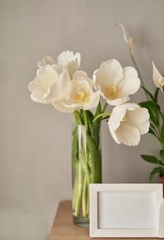 Strauß weißer tulpen und leerer fotorahmen.