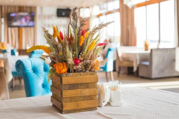 Strauß wilder blumen im restaurant. herbstkomposition in einer holzvase. herbst inneneinrichtung. orange kürbis mit roten beeren, trockenen herbstblumen und gelben blättern. ernte, gemütliche, festliche stimmung.