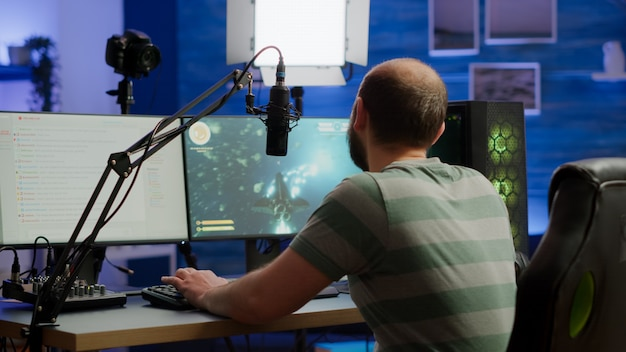 Streamer cyber-performance-weltraum-shooter-videospiel auf einem leistungsstarken rgb-computer, der während des professionellen wettbewerbs mit spielern über stream-chat und mikrofon spricht. spielermann, der im heimstudio streamt