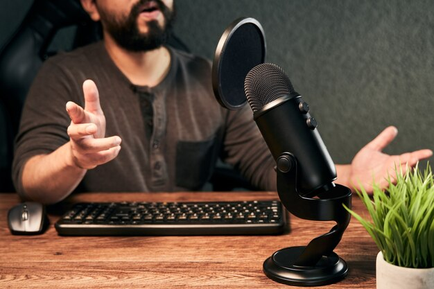 Streamer des jungen mannes, der auf einem mikrofon in einem selbst gemachten studio spricht
