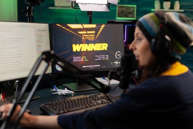 Streamer-frau, die einen virtuellen videospielwettbewerb gewinnt, verwendet professionelle ausrüstung im heimstudio. online-streaming von cyber-performances während eines gaming-turniers mit drahtlosem technologienetzwerk