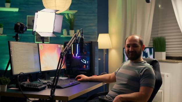 Streamer-mann, der in die kamera schaut und lächelt, während der streaming-chat geöffnet ist