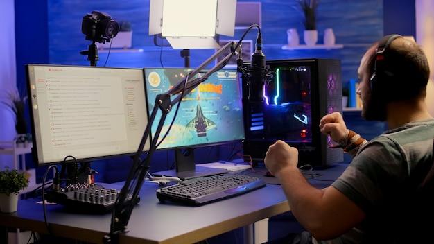 Streamer-mann gewinnt weltraum-shooter-online-wettbewerb mit professionellem mikrofon, tastatur und maus im gaming-heimstudio