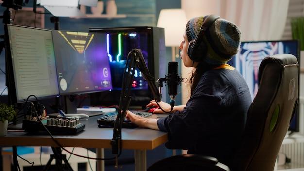 Streamer setzt kopfhörer auf und fängt an, während des professionellen online-videospiel-wettbewerbs mit anderen spielern in das mikrofon zu sprechen. pro gamer sitzt auf gaming-stuhl im streaming-heimstudio mit rg