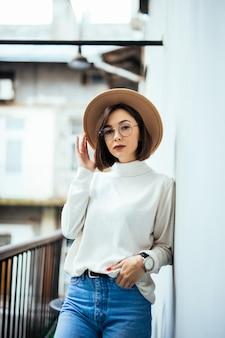 Street fashion interessierte frau mit hut, blue jeans, breitem hut und transparenter brille auf dem balkon
