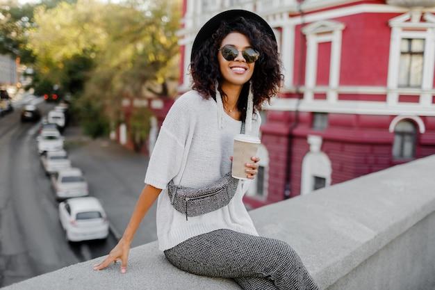 Street fashion look. stilvolles schwarzes mädchen, das auf der brücke sitzt und während ihrer freizeit tasse kaffee oder tee hält. freiberufliche frau. tragen eines schwarzen hutes und einer sonnenbrille.