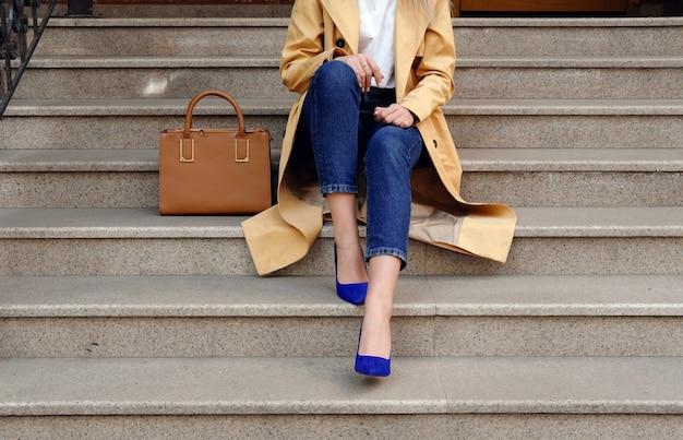 Street fashion outfit, model im blue jeans mantel und große braune lederhandtasche in high heels schuhen sitzen auf der beigen treppe im freien