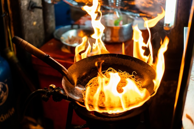 Street food chefkoch braten nudeln in einer schwarzen pfanne mit feuer ausgesetzt. das traditionelle thailändische und chinesische essen in china town in bangkok, thailand.