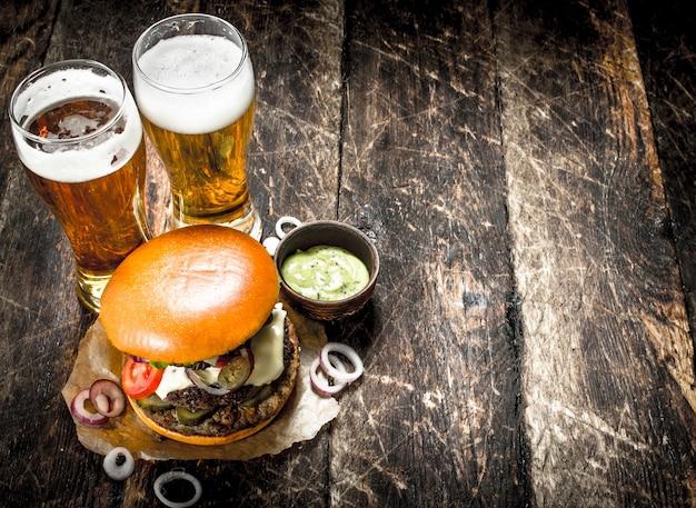 Street food ein großer burger mit gläsern hellem bier auf einem hölzernen hintergrund