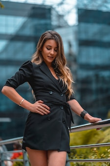 Street style, eine unternehmungslustige junge blonde kaukasische frau in einem schwarzen anzug in dem schwarzen glasgebäude, in dem sie im hintergrund arbeitet. nachdenklich auf den boden schauen