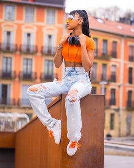 Street style eines jungen trap-tänzers mit zöpfen. ein schönes schwarzes mädchen der afrikanischen ethnischen gruppe mit t-shirt, orange sonnenbrille und cowboyhosensitzen. mit orangefarbenem häuserhintergrund