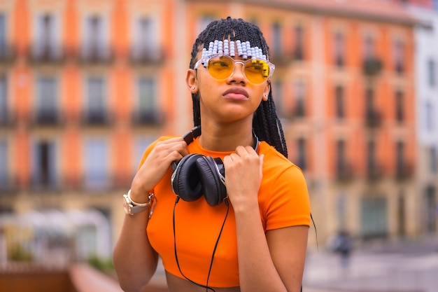 Street style eines jungen trap-tänzers mit zöpfen. sie posiert aus dem schwarzen schleifenmädchen der afrikanischen ethnischen gruppe mit t-shirt, orangefarbener sonnenbrille und sitzender cowboyhose. mit orangefarbenem häuserhintergrund
