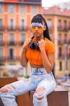 Street style eines jungen trap-tänzers mit zöpfen. sie posiert aus dem schwarzen schleifmädchen der afrikanischen ethnischen gruppe mit orangefarbenem hemd und cowboyhosen. mit orangefarbenem häuserhintergrund