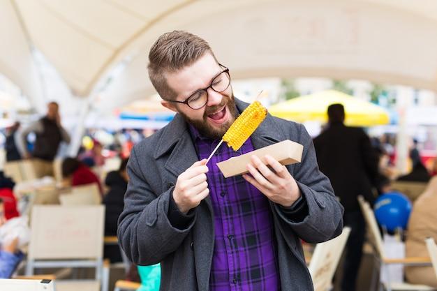 Streetfood- und küchenkonzept - mann, der gegrillten mais isst. vegetarisches essen. gesundes und leckeres gemüse.