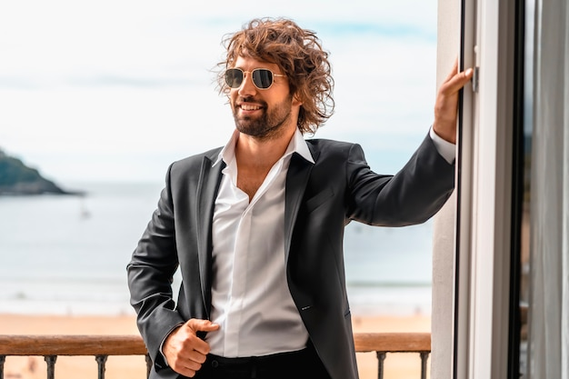 Streetstyle mit einem jungen dunkelhaarigen kaukasischen mann in einem schwarzen anzug und einem weißen hemd in einem luxuriösen hotel mit sonnenbrille.