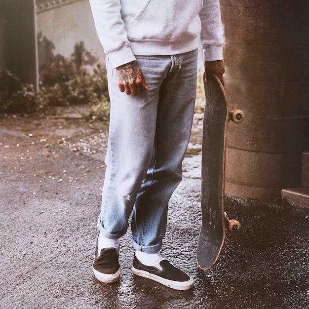Streetwear-modemann mit einem skateboard