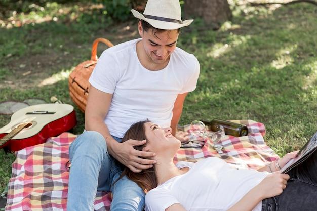 Streichelnde frau des mannes auf einer picknickdecke